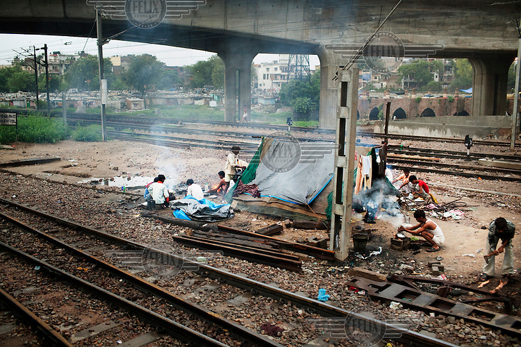 Workers live in a tent along the rail tracks.