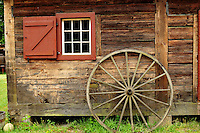 Window, wheel and old wood on the granary, one of the 2 original fort buildings, built in 1850. It is one of the oldest standing buildings in the state of Washington. Fort Nisqually Living History Museum, Point Defiance Park, Tacoma, Washington, USA