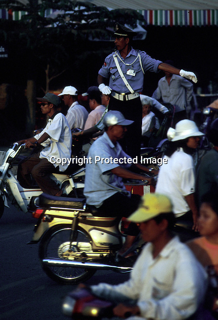 A traffic officer trying to direct the traffic on March 16, 1998 in central Phnom Penh, Cambodia. The cheap imports of mopeds has made the traffic in Phnom Penh grow a lot since he United Nations backed elections in 1992. .(Photo: Per-Anders Pettersson/ Liaison Agency)