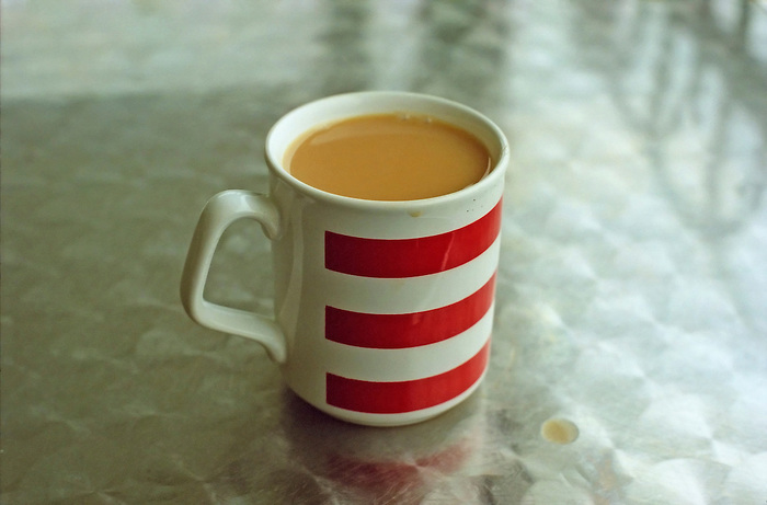 A mug of strong tea on a brushed aluminium cafe table.
