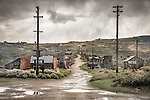 Power poles and mud puddles on the street after a storm in the ghost town of Bodie, California, State Historic Park.