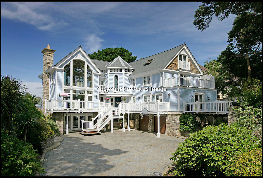 BNPS.co.uk (01202 558833)<br /> Pic Tailormade/BNPS<br /> <br /> 'Tides' - Your for £7.35 million<br /> <br /> 6 bed New England style home with heated pool and boat store.<br /> <br /> The land the global recession forgot.<br /> <br /> Its less than 1 km square but this tiny dot on the Dorset coast contains over £80 million pounds of seafront property on the market or recently sold.<br /> <br /> The millionaire's resort of Sandbanks has been dubbed 'the land the credit crunch forgot' after shrugging off the housing crisis without even a ripple of downturn.<br /> <br /> Despite measuring just half a square mile the posh peninsula in Poole, Dorset, currently boasts more than 70 million pounds worth of property for sale.<br /> <br /> While other areas of the UK have seen house prices drop by up to 20 per cent, the market on Sandbanks has barely flinched, rivalling the most exclusive areas of London.<br /> <br /> Famous faces with luxury villas on the sandy peninsula include football manager Harry Redknapp, his son Jamie and cricketer Geoffrey Boycott.<br /> <br /> It even has its own Russian oligarch - billionaire Maxim Demin moved in after buying a 50 per cent share of Bournemouth's football club in 2011.