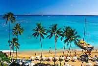 A beatiful view of Waikiki Beach with its palm trees, white sands and catamarans. This view is from the Sheraton Moana Surfrider Hotel.