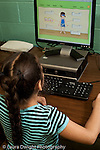 Education Elementary school Grade 2 female student using computer in science computer lab vertical