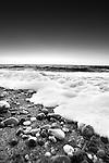 British coastal scene with sea foam on pebbles