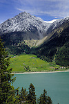 Snow capped mountain and pasture overlooking Lake Resia, Lake Reschensee on the Italian Austrian border.