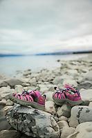 Pink shoes at the edge of Lake Pukaki, Canterbury, New Zealand - stock photo, canvas, fine art print