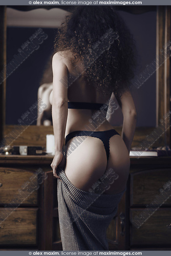 Sensual portrait of back of a sexy woman wearing lingerie dressing up in front of a mirror