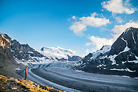 A woman stands looking at the Grand Combin and Glacier de Corbassière at sunset, Val de Bagnes, Switzerland