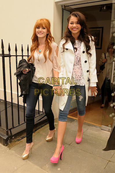 Bella Thorne and Zendaya Cole from the Disney show 'Frenemies' in central London, England..17th May 2012.full length black jeans denim beige top holding hands gold shoes pink shorts jean mac white.CAP/IA.©Ian Allis/Capital Pictures.