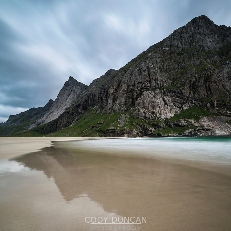 Reflection of mountain peak on Horseid beach, Lofoten Islands, Norway
