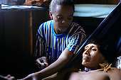 Ipixuna village, Amazon, Brazil. Funai nurse with an Arawete patient in the health post checking pulse.