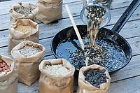 Selbstgemachte Fettfuttermischung, Kokosfett wurde in der Pfanne erhitzt, nun wird eine Körnermischung hinzugeschüttet, Fettfutter aus Kokosfett, Sonenblumenkernen, Erdnussbruch, Körnermix, Körnermischung, Sonnenblumenöl, Vogelfutter selbst herstellen, Vogelfutter selber machen, Vogelfutter selbermachen, Vogelfütterung, Fütterung, bird's feeding