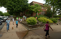 NWA Democrat-Gazette/ANDY SHUPE<br /> Visitors walk Thursday, July 5, 2018, past the Old Post Office building during First Thursday on the Fayetteville square. The building, which has been home to several businesses, recently sold.