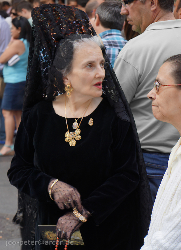 old catholic woman in religious parade in Granada dressed elegantly in traditional black gown