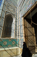 A woman in a chador passes through the huge carved wooden doors and the magnificent blue tiled entrance portal to the 15th century Jameh (Friday) Mosque in Yazd, Iran.