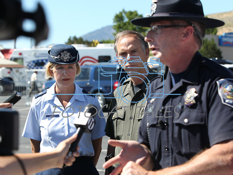 Nevada National Guard Press Information Officer April Conway, left, and Carson City Sheriff Ken Furlon, center, listen to Trooper Chuck Allen at a press conference following a shooting in an IHOP restaurant in Carson City, Nev., on Tuesday, Sept. 6, 2011. (AP Photo/Cathleen Allison)