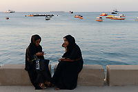 TANZANIA, Zanzibar, Stone town, two muslim women with smart phone at seafront