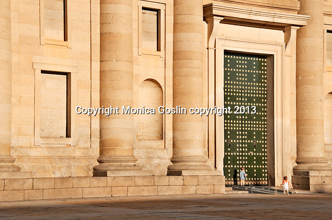 El Escorial is a historical residence of the kind of Spain and serves as a royal palace, museum, school and monastery that date back to the 16th and 17th centuries; here you see the giant scale of the building and doors against the small children