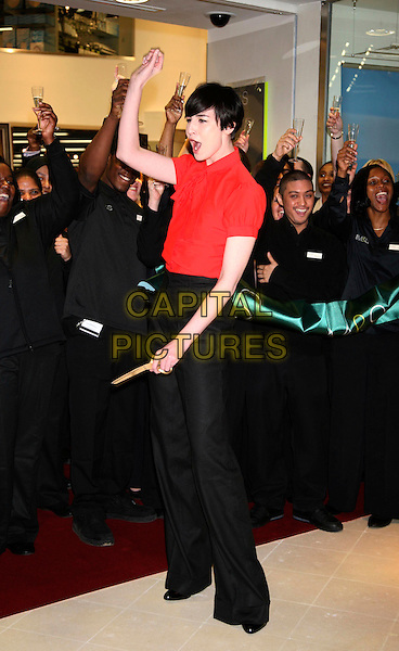 ERIN O'CONNOR.Opens the new M&S store at Colliers Wood, South London, England..May 1st, 2008.M & S Marks & Spencer full length red blouse tie black trousers arm in air cheering mouth open funny face .CAP/DS.©Dudley Smith/Capital Pictures
