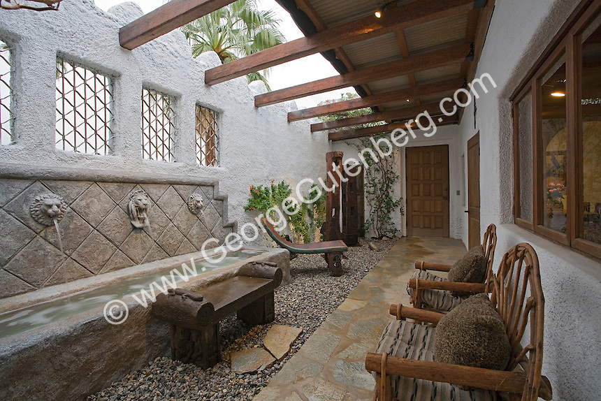 Outdoor room features ethic primitive art object in enclosed open air patio