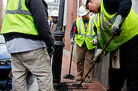 Jerome Whitaker (from left), Aroll Victor, Lionel Hampton, and David Dollosa, repair a sidewalk while working for the Boston Public Works Department in Boston, Massachusetts, USA, on April 12, 2012. The city uses a computer system to track public complaints and record work done by city crews to mitigate these complaints.  A supervisor or inspector photographs before and after pictures of the work in addition to making notes about the work done.