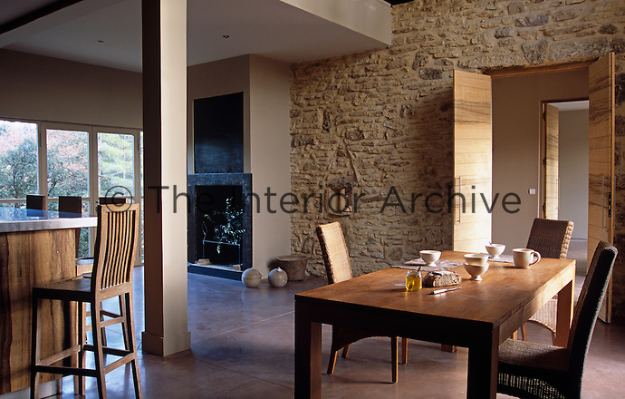 A rustic stone wall dominates one side of the rustic yet contemporary kitchen/dining room