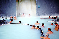 People lounge in the Blue Lagoon Geothermal Spa in Grindavík, Iceland. The pool is warmed by the energy from a nearby geothermal power plant.
