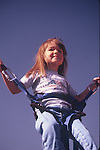 YOUNG CHILD IN BUNGEE SWING AT PUMPKIN FESTIVAL