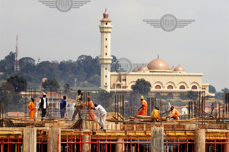 Construction workers labour on a building site in front of the Kampala Mosque also known as the National Mosque or the Gaddafi National Mosque; as the late dictator paid for its construction.