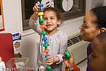 Education preschool 4 year olds manigpulatives girl happily making peg tower while female teacher looks on and encourges her horizontal