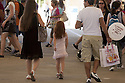 A little girl with a golden crown on his head struts accompanied by his parents along the Decumanus, the main avenue of Expo 2015, Rho-Pero, Milan, in June 2015. &copy; Carlo Cerchioli<br /> <br /> Una bambina con una coroncina dorata cammina accompagnata dai genitori lungo il Decumano, il principale viale di Expo 2015, Rho-Pero, Milano, giugno 2015.