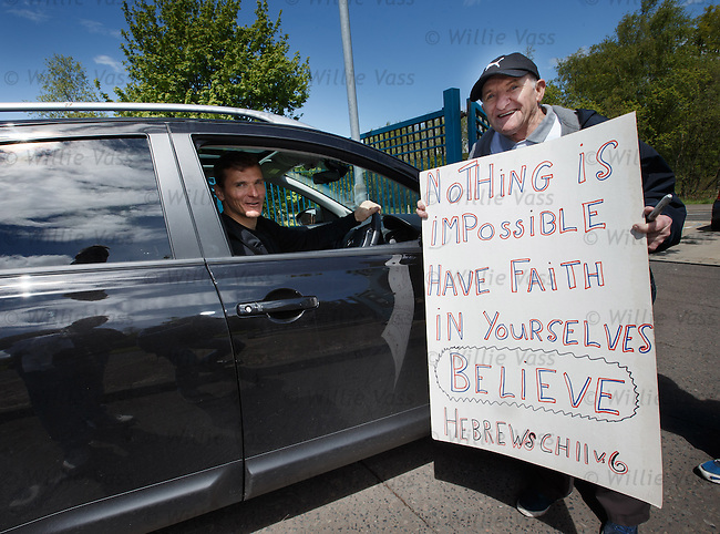 Captain Lee McCulloch leaves Murray Park after training and pauses to read a motivational sign at the gates