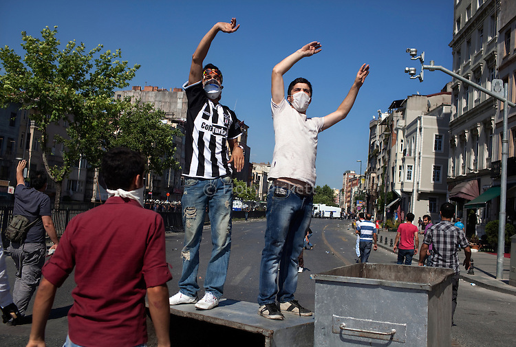Protesters urge others to come toward police on one of Istanbul's main thoroughfares, Tarlabasi Street, Istanbul, Turkey, June 1, 2013. What started as a peaceful sit-in to save a small park near Taksim Square from being turned into a shopping mall has turned into large-scale anti-government demonstrations in cities across Turkey.
