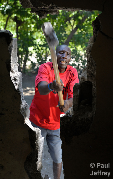 Wilson Innocent tears down the wall of his earthquake-damaged mother's house in Mellier, Haiti. The dwelling will soon be replaced with a new house provided by the United Methodist Committee on Relief (UMCOR).