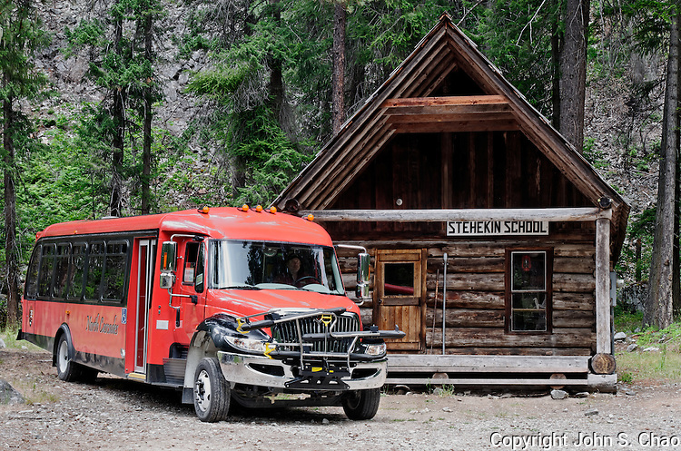 North Cascades National Park Red Tourbus with historic Stehekin Schoolhouse, Stehekin, Washington State.