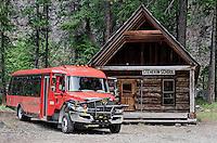 North Cascades National Park Red Tourbus with historic Stehekin Schoolhouse, Stehekin, Washington State.
