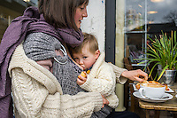 A mother breastfeeds her 15 month old boy who is in a sling and holding a piece of bread.<br /> <br /> London, England, UK<br /> 22-03-2015<br /> <br /> © Paul Carter / wdiip.co.uk