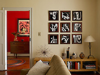 A view of the red hallway from the living room includes charcoal illustrations of smoke rings by Ben Veronis