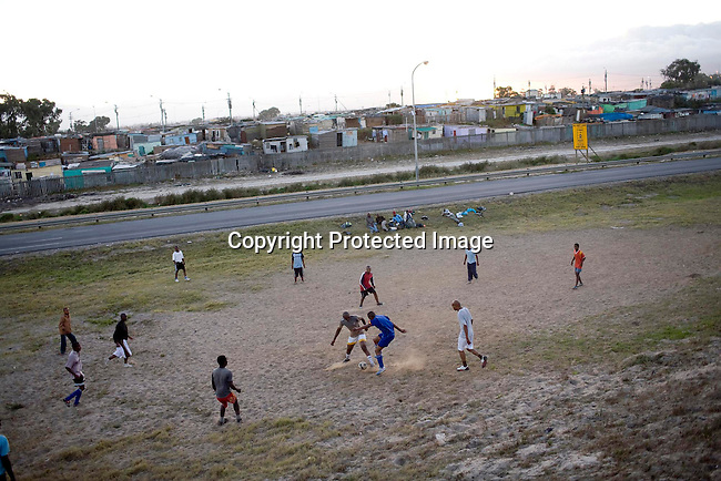 A youth soccer team trains along the N2 highway next the Cape Town airport close to Nyanga, a poor township on February 20, 2008 outside Cape Town, South Africa. Photography by Per-Anders Pettersson/Reportage by Getty Images for ESPN Magazine..