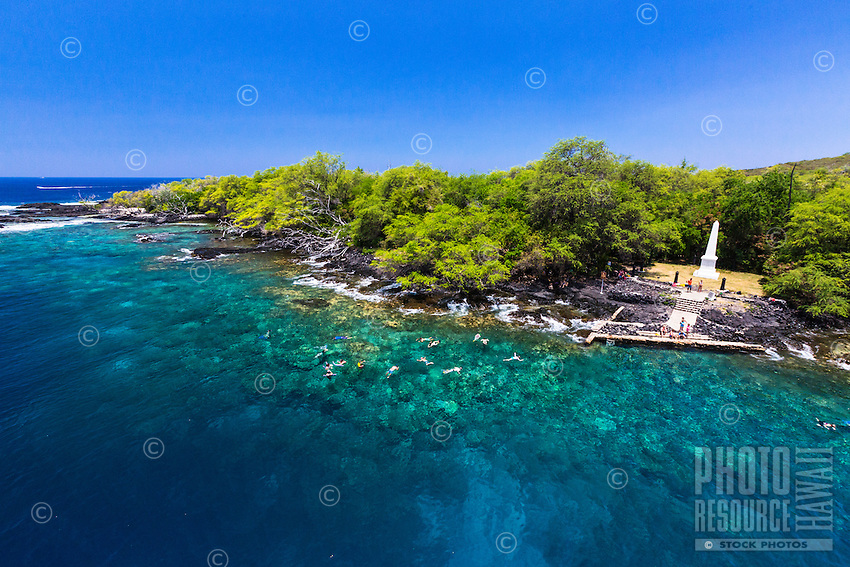 Tourists snorkel in the clear waters of the Big Island's Kealakekua Bay. On the right, visitors stand near the Captain Cook Monument.