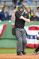 Home plate umpire Marc Lindsey calls a strike on the Kane County Cougars against the Clinton LumberKings at Ashford University Field on July 5, 2014 in Clinton, Iowa. The Cougars won 4-0.   (Dennis Hubbard/Four Seam Images)