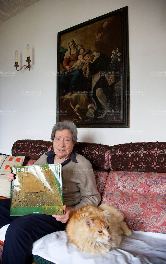 "Switzerland. Canton Ticino. Blenio valley. Ludiano. Luciana Pally Ferrari seats on a sofa at home with her cat. She holds in her arms a book "" La France vue d'en haut"", a gift from Manuel Valls (the french politician). Ludiano is part of the municipality Serravalle. 3.04.2014 © 2014 Didier Ruef"