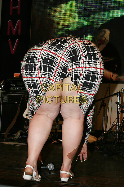 BETH DITTO - THE GOSSIP.Live in concert at HMV, London, England..May 3rd, 2007.gig performance music full length grey gray white red plaid tartan dress cellulite back behind rear birthmark flashing .CAP/MAR.© Martin Harris/Capital Pictures.