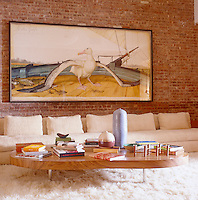 On the exposed brick wall of the media room a Walton Ford Albatross hangs above an 18-foot sofa arranged on a fluffy Flokati rug with a teak coffee table piled with books