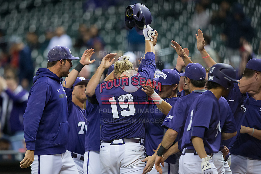 Luken Baker (19) of the Texas Christian Horned Frogs is greeted by his teammates after hitting a home run against the Rice Owls during game six of the Shriners Hospitals for Children College Classic at Minute Maid Park on February 27, 2016 in Houston, Texas.  (Brian Westerholt/Four Seam Images)