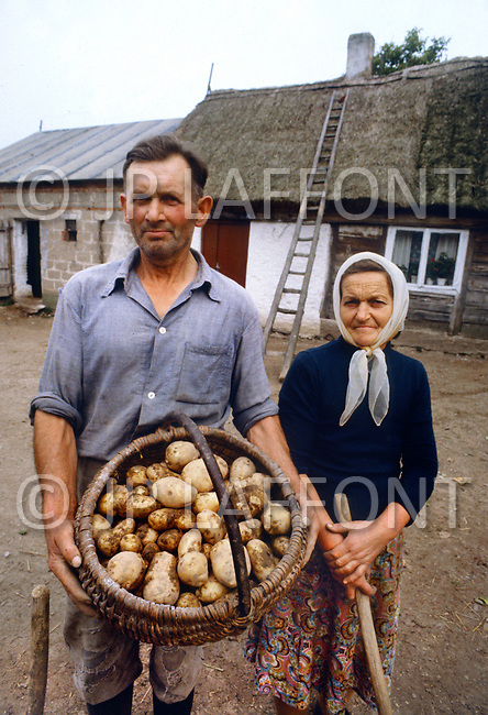 Poland, September, 1981 - Chicken farmers in Torun. They live off the sale of chicken and eggs, augmented by a small garden where they grow potatoes. The farm where they live is very traditional and old-fashioned.<br /> Pologne, septembre 1981 &ndash; Ces &eacute;leveurs vivent de la vente de leurs poulets, de leurs &oelig;ufs et d&rsquo;une petite r&eacute;colte de pomme de terre. Ils vivent dans une vielle maison traditionnelle au toit de chaume.