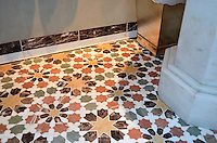 This custom bathroom floor features Granada Grande, a waterjet mosaic shown in polished Emperador Dark, Verde Luna, Rosa Verona, Calacatta Tia, and Giallo Reale, is part of the Miraflores collection by Paul Schatz for New Ravenna.<br />