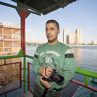 Egypt / Cairo / 4.4.2013 / Mohamed Elmaymony, Egyptian photographer, poses with his camera along the Nile, in Cairo. © Giulia Marchi