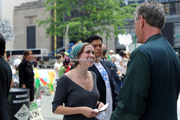 Brad Kunde (right), 60, on his lunch break from the Chicago Board of Options challenged Halle Miroglotta (left), 19, a student at Loyola University on the utility of clean energy at a lunch-time protest organized by several groups including the Little Village Environmental Justice Organization and the Rainforest Action Network in the Daley Center in downtown Chicago, Illinois on June 8, 2009.